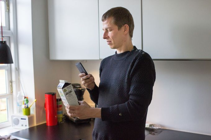 Visually impaired man video chatting to check the expiry date on a milk carton.
